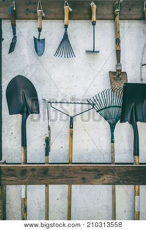 Metal gardening tools put to slot made from wood and hang up tidy on nails. Example of tool are shovel spade harrow rake and shovel forks. Vintage film filter effect. Agricultural equipment stories