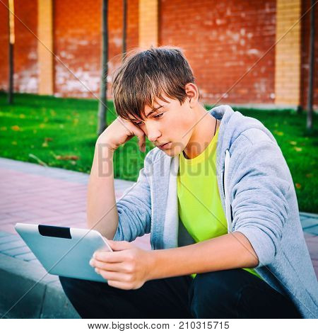 Toned Photo of Sad Teenager with Tablet Computer on the Street
