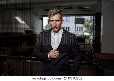 Handsome young man in classy suit posing and looking at camera.