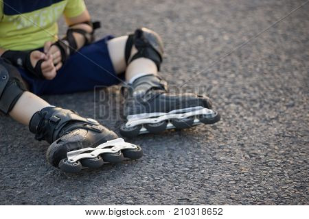 Top view and closeup of child's legs in professional roller blades. Boy sitting on asphalt and relaxing after active rollerblading. Sport activities outdoors. Lifestyle