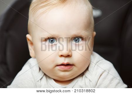 Adorable baby with plump cheeks, big beautiful eyes and long lashes looks directly in camera with earnest air portrait photo. Cute little blond boy.