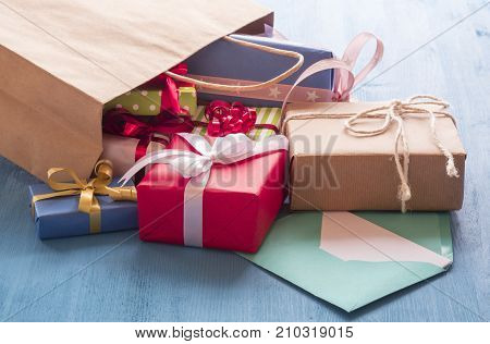 Shopping bag with gift boxes - Colorful gift boxes coming out on a blue wooden table from a paper shopping bag