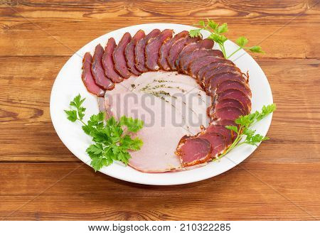 Sliced boiled-smoked pork loin and cured pork tenderloin decorated with parsley twigs on a white dish on an old wooden surface
