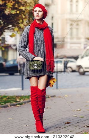 Outdoor full body portrait of young beautiful fashionable woman wearing trendy red high, over knee boots, stylish clothes and accessories. Model posing in street. Elegant autumn outfit. Female fashion
