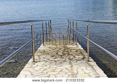 paved sea ramp with metal fence and handrail