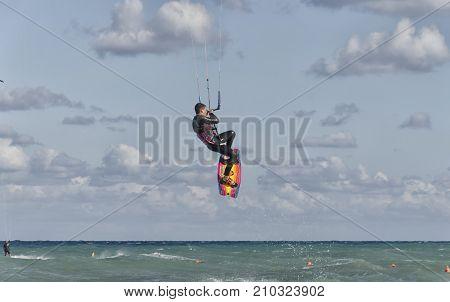 Cesine Italy - September 21 2017: Kitesurfer while making an acrobatic leap
