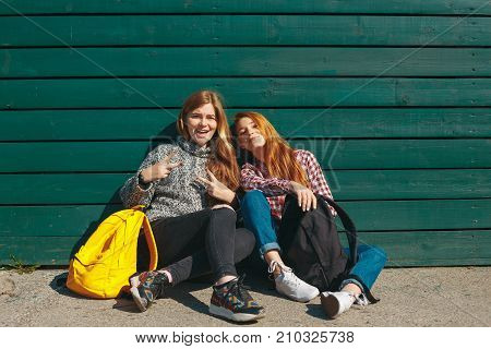 Friendship concept. Natural reddish hipster girls having fun on a green wooden background. Cheerful friends spending time together. Smiling girls with backpacks relaxing in an autumn sunny day.