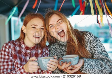 People, communication and friendship concept - Portrait of cheerful young women holding coffee cups with hands looking to camera while winking saying something. Two natural reddish girls with freckles