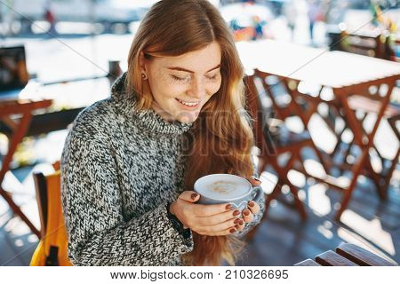 Coffee concept. Young woman happy to hold a hot cup of coffe outdoors. Natural reddish girl with freckles, dressed in soft wool sweater, smiling while holding a big cup of coffee latte.
