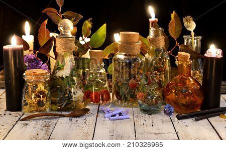 Glass bottles with potions and herbs and black candle on witch table. Occult, esoteric, divination and wicca concept. Alternative medicine and homeopathic vintage background poster