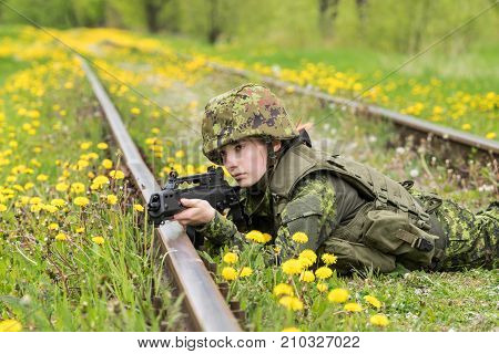 Portrait of armed woman with camouflage. Young female soldier observe with firearm on rail. Child soldier with gun in war green grass and yellow dandelions background. Military army people concept