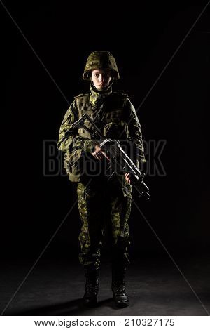 Portrait of armed woman with camouflage. Young female soldier observe with firearm. Child soldier with gun in war black background. Military army people concept