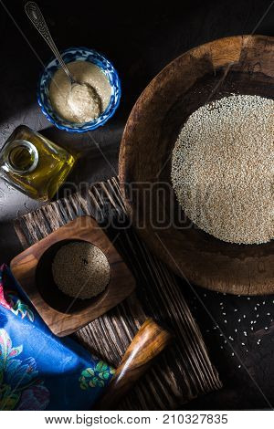 Tahini in a bowl of sesame seeds and olive oil vertical