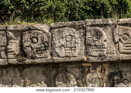 Carved scull wall on execution site at Mayan pyramid chichen itza mexico