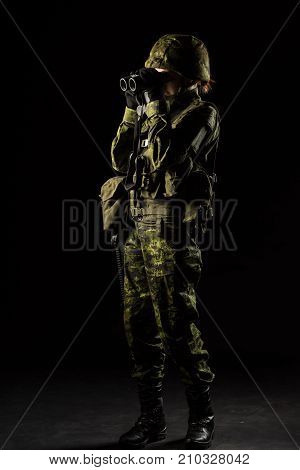 Portrait of armed woman with camouflage. Young female soldier observe with binoculars. Child soldier with gun in war black background. Military army people concept