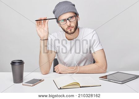 Professional male worker with thick beard and trendy hat wears square glasses casual t-shirt at work place drinks coffee works with documents. Hipster young guy being busy working on new project.