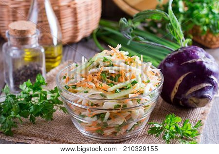 Fresh salad with kohlrabi cucumber carrots and herbs in a bowl. Vegetarian food. Tasty and healthy dish. Healthy eating