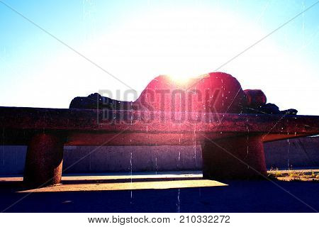 Flare soft focus. Silhouette in sunbath. Drank adult man rests on stony bench in park Sharp sun rays make contours around sleeping body.