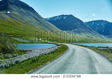 Travel to Iceland. beautiful sunrise over the ocean and fjord in Iceland. Icelandic landscape with mountains, blue sky and green grass on the foreground. View of the road in the north-west of Iceland, on the Westfirdir peninsula