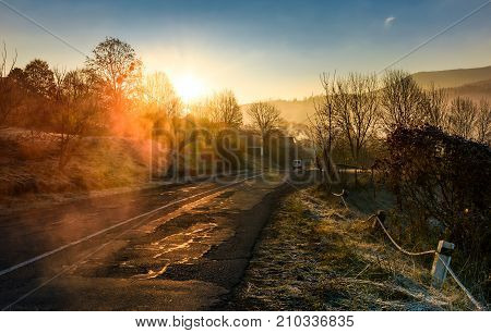 Road Through Mountain Village At Foggy Sunrise