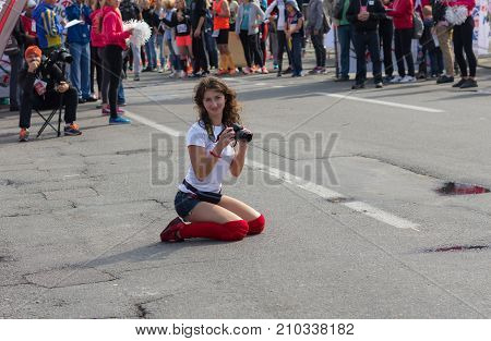DNEPR UKRAINE - SEPTEMBER 24 2017:Cute female amateur photographer sitting on a street and waiting for a finisher for to make cool shot during