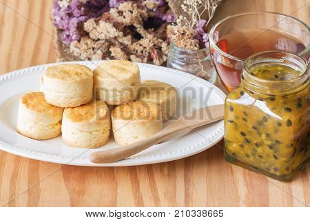Homemade delicious plain scones with homemade passion fruit jam and tea in horizontal vintage tone style for background or wallpaper. Scones is English pastry for afternoon tea or coffee break. Scone and passion fruit jam served with tea.