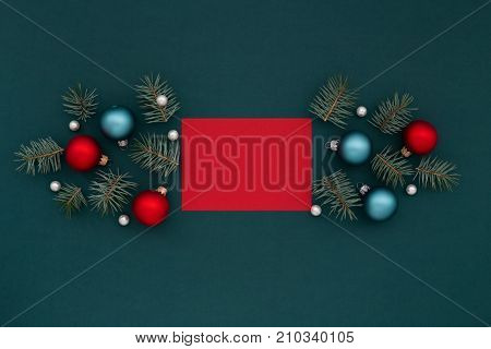 Red greeting card and Christmas decorations balls fir pearls on Shaded spruce background. Holidays New Year congratulation.
