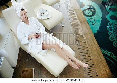 High angle portrait of beautiful young woman smiling at camera relaxing in lounge chair by swimming pool wearing bath robe