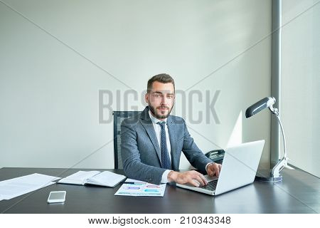 Waist-up portrait of handsome bearded manager in classical suit posing for photography while sitting at office desk and working on promising project with help of laptop.