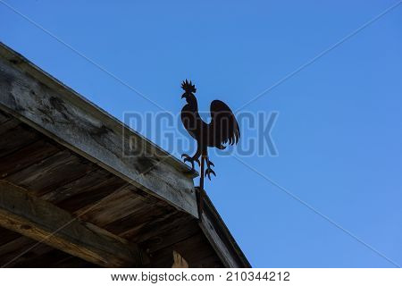 Cock - weathervane on the roof. House eaves and blue sky evening light. Pitburger See Taxegg Salzburg Austria Europe