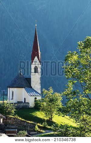 Chapel on the meadow. Bell tower trees shrubs and hilly green grassland. Heiliger Antoniuse church and houses in the evening light. Pitburger See Taxegg Salzburg Austria Europe
