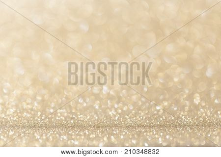 Light gold (yellow) glitter background. Sparkle texture. Abstract gradient twinkle background blurred for New Years or Christmas holiday