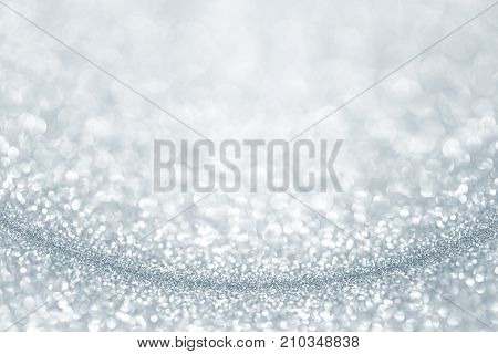 Silver light blue glitter background. Sparkle texture. Abstract gradient twinkle background blurred for New Years or Christmas holiday