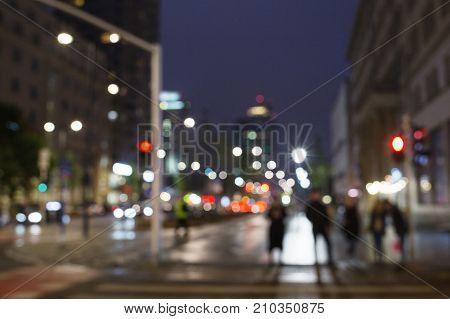 Blurred night city life. Traffic light people night lights. Urban background