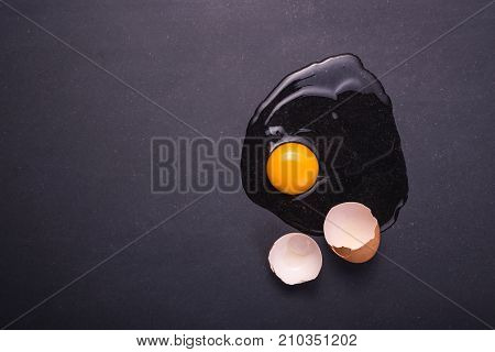 Broken Eggs On The Black Stone Ground. Free Space For Text And Design. Top View