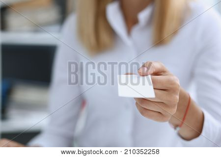 Female hand in suit give blank calling card to male visitor closeup. White collar partners company name exchange executive or ceo introducing at conference product consultant sale clerk concept