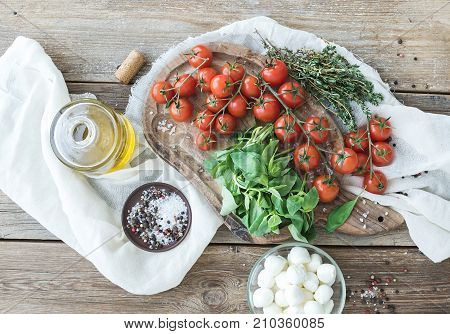 Basil, cherry-tomatoes, mozarella, olive oil, salt, spices on rustic chopping board over old wood background. Top view