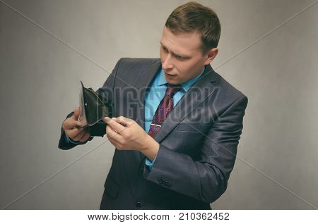 Young business man in a suit holds an empty wallet in his hand and looks for money in it. Pay the debt. Bankruptcy concept. poster