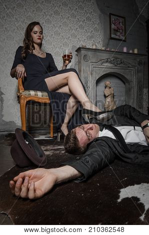 Film scene. Femme Fatale committed murder. Beautiful woman sits near dead body of detective. Body of man lying on floor. Woman holding glass of whiskey.