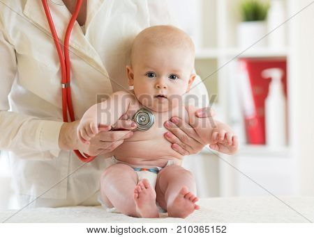 Doctor pediatric examining baby in clinic. Child health concept