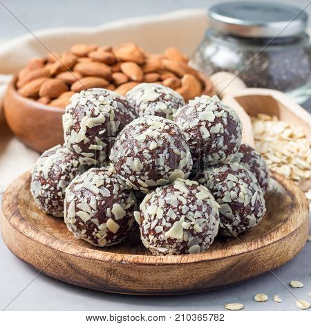 Healthy homemade paleo chocolate energy balls on wooden plate square format