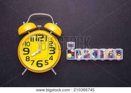 7 Day Plastic Pill Organizer And Yellow Alarm Clock On Dark Table. Time To Take Pill Concept. Top Vi