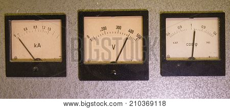 Three old analog instruments - Power factor meter, voltmeter and ampere meter isolated on grey background.