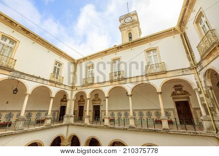 Coimbra, Portugal - August 14, 2017: cloister inside University of Coimbra, the Europe's oldest university founded in 1290. Iconic Clock Tower on background, a important tourist attraction in Coimbra.