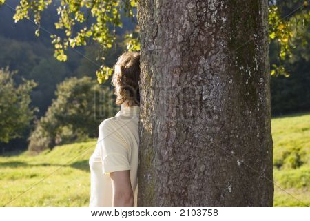 Woman Leaning At A Tree At Sunset