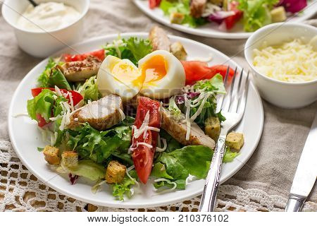 Caesar salad with lettuce tomato grilled chicken cheese and soft-boiled egg