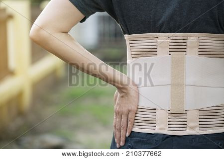 young asian woman wearing back support for protect her back medicine and healthy concept