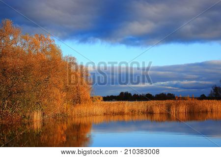 Autumn nature. Autumn forest. Blue lake water. The autumn woods. Golden autumn. Lake in autumn forest. Autumn forest reflected in the lake in september. Autumn landscape. Russian forest in autumn. Autumn forest in Sunny day. The lake in Russia