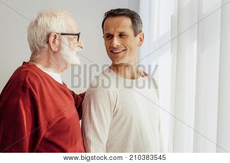 Ask me later. Attractive young man feeling happiness while spending time with his granddaddy