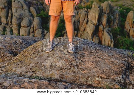 Photo of male legs in gumshoes on the background of the canyon